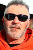 Unshaven Laborer Wearing Sunglasses. A closeup portrait of an older unshaven laborer wearing sunglasses and an orange construction caution hooded sweat shirt Stock Photography