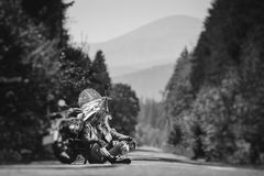 Unshaven male biker sitting on dirt road near motorcycle Stock Photography