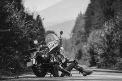 Unshaven male biker sitting on dirt road near motorcycle. Handsome biker with beard and long hair sitting next to a traveler motorcycle on an open road. Sunny Stock Image