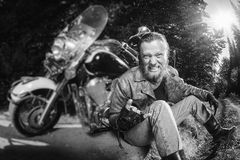 Unshaven male biker sitting on dirt road near motorcycle. Unshaven male biker in leather jacket and jeans sitting on road near motorcycle and giving the devil Stock Image
