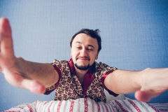 Unshaven man in bed stretching Royalty Free Stock Photo
