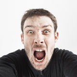 Unshaven man in a black jacket on a white background shouts.  Stock Image