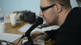 Unshaven man in glasses speaks into the microphone. He had reddish hair and very short haircut, he fiddles with the knob, he says into the microphone and makes stock video
