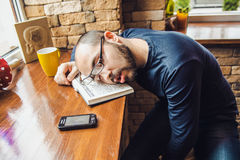 Unshaven man in glasses tired, fell asleep at the table Royalty Free Stock Photo