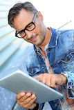 Unshaven man holding tablet in street Royalty Free Stock Photos