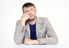 Unshaven man in a jacket is sitting at a table, he dreams Stock Photography