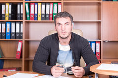 Unshaven man in office with pen Royalty Free Stock Photography