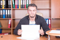 Unshaven man in office with sheet of paper Royalty Free Stock Image