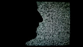 Unshaven man profile silhouette in front of static TV noise background. stock video footage