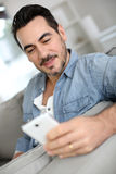 Unshaven man readig message from smartphone Royalty Free Stock Photography