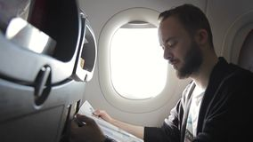 An unshaven man is reading a magazine in a plane near porthole. Male passenger learns the press during a flight in an air company stock video