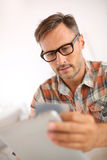 Unshaven man shopping online with tablet Stock Image