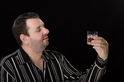Unshaven man wants to drink brandy Royalty Free Stock Photography