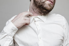 The unshaven man in the white shirt is tight and stuffy. And he tries to expand the collar to make a breath Royalty Free Stock Photos