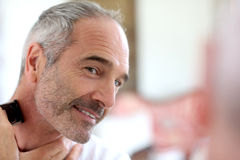 Unshaven mature man using razor Royalty Free Stock Photos