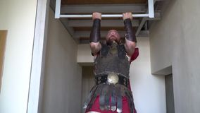 Unshaven Roman gladiator in leather armor pulls up on a horizontal bar in the corridor. Unshaven bald Roman gladiator in armor pulls up on the bar in the stock video footage
