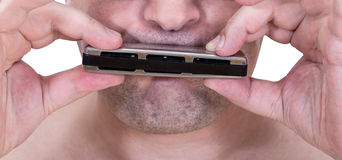Unshaven strolling musician playing harmonica Royalty Free Stock Image