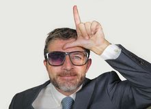 Unshaven and werid businessman in weird broken nerdy glasses and stupid smile doing loser sign with L fingers signal on forehead stock images