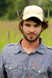 Unshaven young man. An unshaven young man with a beard and a ball cap standing in tall grass. Shallow depth of field Stock Photography