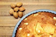 Unshelled almond nuts next to a freshly baked frangipane tart or cake.  Stock Photos