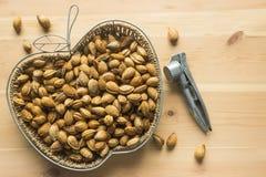 Unshelled almonds in a wicker basket. Metal Nutcracker lying on Royalty Free Stock Photo
