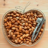 Unshelled almonds in a wicker basket. Metal Nutcracker lying on Stock Image