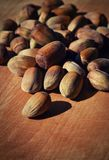 Unshelled hazelnuts. On a wooden board still life Royalty Free Stock Image