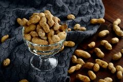 Unshelled peanuts in a glass bowl. On the table Royalty Free Stock Photo