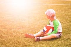 Unsicheres Baby, das nahe bei Fußball am Fußballplatz sitzt Fußballtrainingskonzept stockfotografie