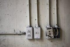 Unsicherheit elektrisch und Netzstecker mit Rohr auf der alten Schmutzwand lizenzfreie stockfotos
