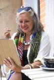Unsing mobil enhet för mogen kvinna i kafé Arkivbilder