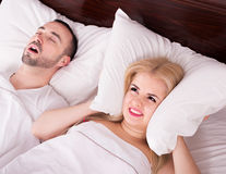 Unsleeping woman and snoring man. Upset young women cannot sleep because of boyfriend snores loudly Stock Photos