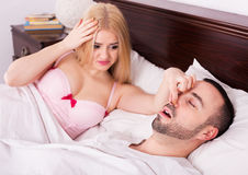 Unsleeping woman and snoring man. Young women cannot sleep because of boyfriend snores loudly Royalty Free Stock Photo