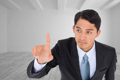Unsmiling asian businessman pointing Stock Photo