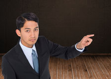 Unsmiling asian businessman pointing Royalty Free Stock Images