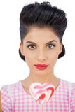 Unsmiling black hair model holding a heart shaped lollipop Royalty Free Stock Image