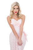 Unsmiling blonde model in pink dress posing looking at camera an Stock Images