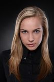 Unsmiling, blonde teenager in black. Studio portrait of unsmiling, blonde teenager in black, black background Royalty Free Stock Photos