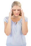 Unsmiling blonde woman has headache Royalty Free Stock Images