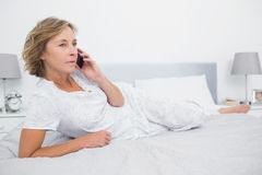 Unsmiling blonde woman lying on bed making a phone call. Unsmiling blonde women lying on bed making a phone call in bedroom at home Royalty Free Stock Images