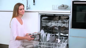 Unsmiling blonde woman put her dishes in dishwasher in kitchen stock video footage