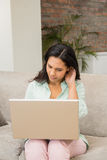 Unsmiling brunette using laptop Royalty Free Stock Photo