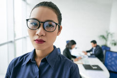 Unsmiling business woman. Face of young unsmiling Asian business lady in glasses Stock Photos