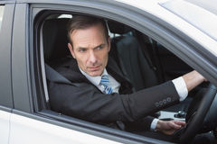Unsmiling businessman in the drivers seat Royalty Free Stock Photo