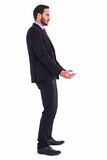 Unsmiling businessman holding something with his hands Royalty Free Stock Image