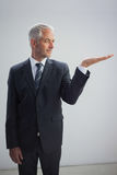 Unsmiling businessman presenting something Royalty Free Stock Photo