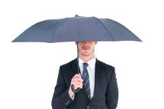 Unsmiling businessman sheltering under umbrella Stock Images