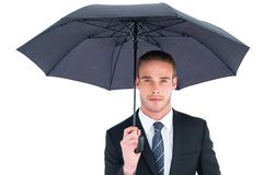 Unsmiling businessman sheltering under umbrella. On white background Stock Image