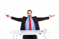Unsmiling businessman sitting with arms outstretched Stock Photos