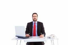 Unsmiling businessman sitting at desk Stock Photo